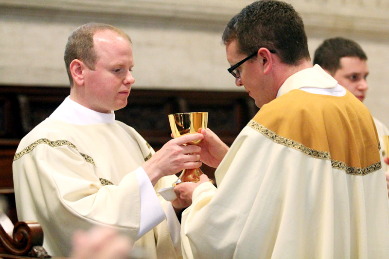 Matthew Windle offers blood of Christ to Fr Tom Gardner