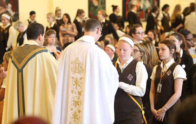 Fr Ronald Check distributes communion to junior Liz Schule