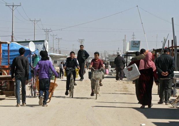 Syrian refugees walk the street at Zaatari refugee camp near Mafraq, Jordan, March 14. Jordan officials report international aid continues to fall short of what the country needs to host 1.4 million Syrian refugees. (CNS photo/Jamal Nasrallah, EPA)