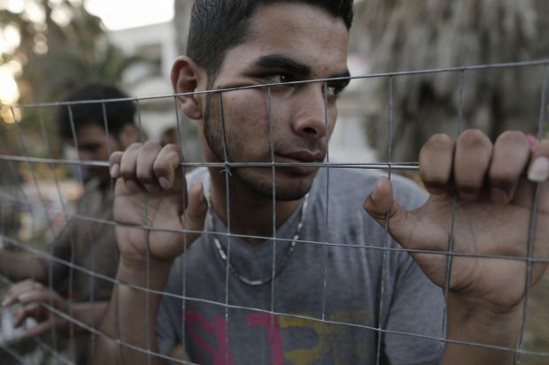 An Afghan refugee stands behind a fence at the yard of an abandoned hotel on the island of Kos, near the sea border with Turkey and Greece, May 6. (CNS photo/Yannis Kolesdis, EPA)