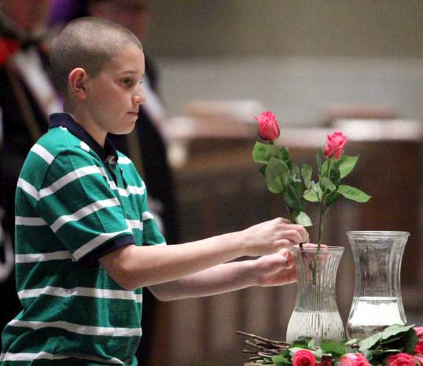 Jimmy from Presentation BVM places a rose for the blessed mother