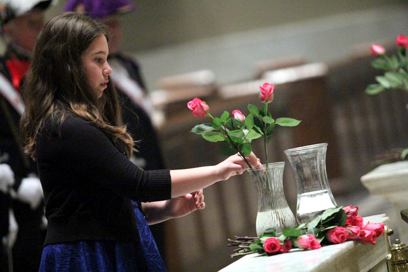 Olivia de Silva from the May Court places a rose in a vase that will be placed before the blessed mother