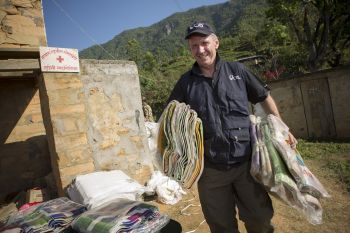 Greg Auberry, Catholic Relief Services' regional director for East and South Asia, carries blankets for earthquake victims near a village in Gorkha, Nepal, May 3. (CNS photo/Jake Lyell, CRS)