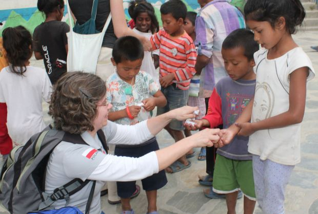 Marta Titaniec, projects coordinator of Caritas Poland, distributes sweets to inmates of the Children's Home for prisoners' children at Sankhu village outside Kathmandu, Nepal, May 7. Caritas Poland has brought a Polish air force plane with 16 tons of relief material for the victims of the April 25 Nepal earthquake. (CNS photo/Anto Akkara).