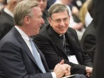 "Swiss Cardinal Kurt Koch, president of the Pontifical Council for Promoting Christian Unity, center, smiles alongside John Garvey, president of The Catholic University of America at the university in Washington May 19. They attended ""Nostra Aetate: Celebrating Fifty Years of the Catholic Church's Dialogue with Jews and Muslims, a three-day symposium of scholars, which the cardinal addressed May 20. (CNS photo/Ed Pfueller, Catholic University of America)"