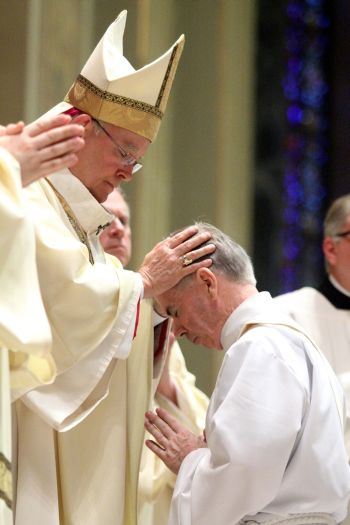 Archbishop Chaput lays hands on Father Kevin Mulligan, ordaining him a priest for the Archdiocese of Philadelphia. (Sarah Webb)