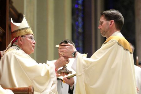 Father Joseph Zaleski receives the chalice and paten from the archbishop during the rite. (Sarah Webb)