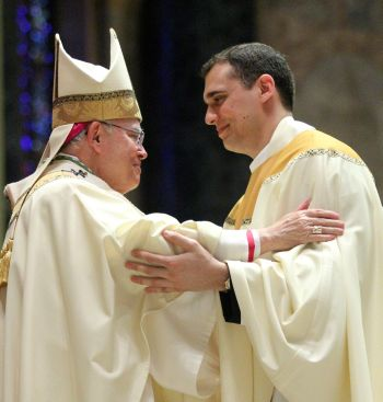 Father Daniel Arechabala exchanges the sign of peace with Archbishop Chaput during the ordination liturgy. (Sarah Webb)