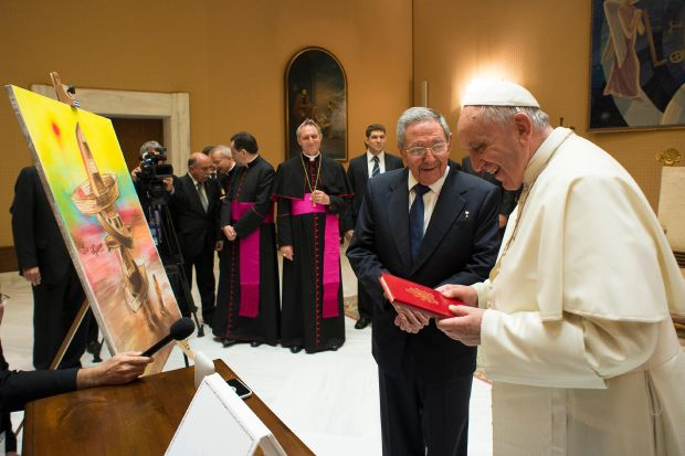 Pope Francis exchanges gifts with Cuban President Raul Castro during a private audience at the Vatican May 10. The painting shows a cross made up of migrants' boats with a migrant kneeling before it in prayer. Castro gave the painting to the pope. (CNS photo/L'Osservatore Romano, pool)