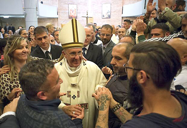 Pope Francis greets inmates after celebrating Mass on Holy Thursday, April 2, at Rebibbia prison in Rome. The pope regularly visits with prisoners, a practice he began while archbishop of Buenos Aires. (CNS photo/L'Osservatore Romano via Reuters)