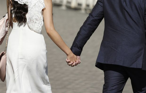 A newly married couple hold hands as they arrive for Pope Francis' general audience in St. Peter's Square at the Vatican May 27. (CNS photo/Paul Haring) See POPE-AUDIENCE May 27, 2015.