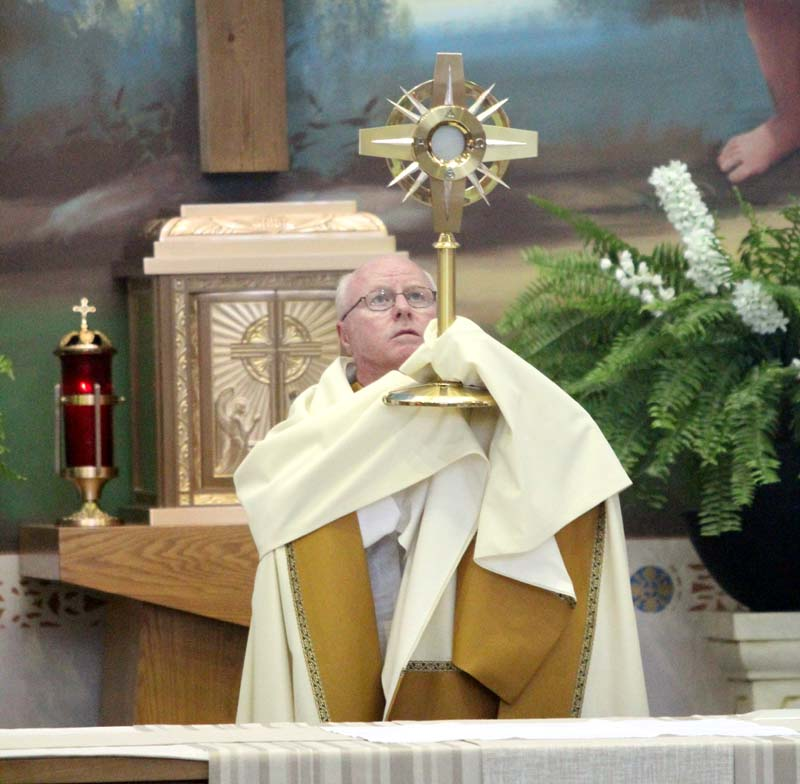 Msgr. Joseph Prior leads benediction of the Most Blessed Sacrament at his  parish, St. John the Evangelist. (Sarah Webb)