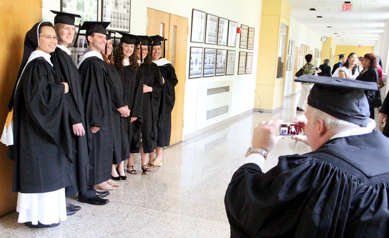 Graduates pose for a quick picture before walking up the aisle