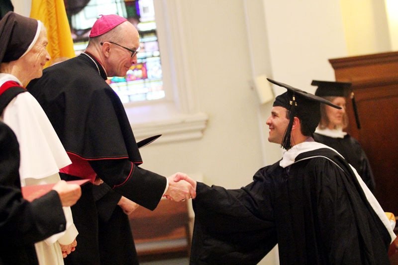Brian Jefferes shaking Bishop Senior's hand as he recives his Master of Arts Degree while  Mother Assumpta Long, O.P. looks on