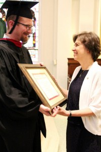 Jared Hasslebarth presents the posthumous degree to Paula Miola for her husband Steven R. Miola who recently passed away