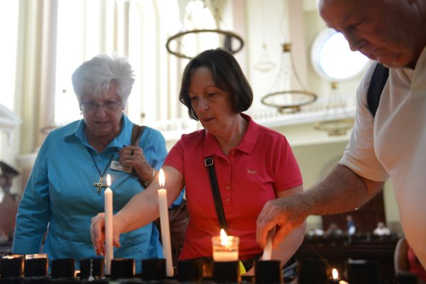 U.S. pilgrims light candles in the cathedral in San Salvador May 21, two days before the beatification of Archbishop Oscar Romero. Archbishop Romero was shot by unidentified gunmen as he celebrated Mass March 24, 1980. (CNS photo/Lissette Lemus)