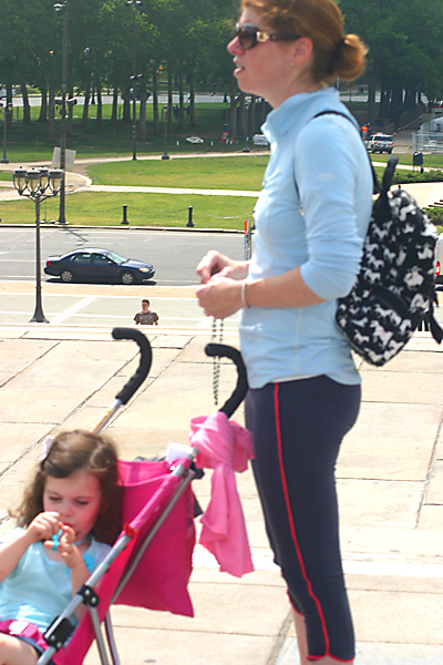 Kate East (left) takes in the scenery at the Art Museum in her stroller as her mom, Ginny, of St. Patrick Parish in Malvern, prays the rosary.