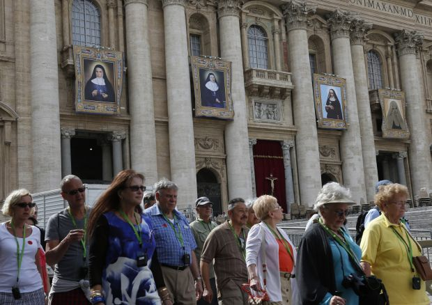 Banners showing Blesseds Marie-Alphonsine, Jeanne Emilie De Villeneuve, Maria Cristina Brando and Mary of Jesus Crucified hang from the facade of St. Peter's Basilica at the Vatican May 15. The four will be canonized May 17 by Pope Francis. (CNS photo/Paul Haring)
