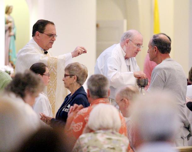 pastor Fr Kramer and Fr Ronan give communion