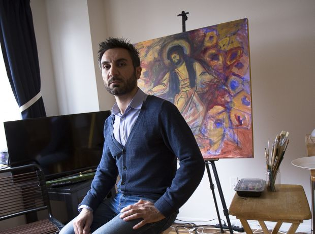 Essa Neima poses for a photo in his art studio in Washington.  The Syrian artist said he got the idea to showcase his country's struggles after extremists killed a Jesuit priest friend there. (CNS photo/Tyler Orsburn)