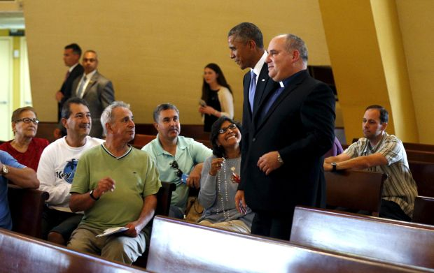 U.S. President Barack Obama makes an unannounced stop to the Shrine of Our Lady of Charity in Miami, Florida May 28. Walking with the president is Father Juan Rumin Dominguez. The shrine is named for the patroness of Cuba and the Cuban people. (CNS photo/Kevin Lamarque, Reuters)