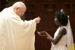 Roberteliane Seant receives Communion for the first time from Father John LaRosa.