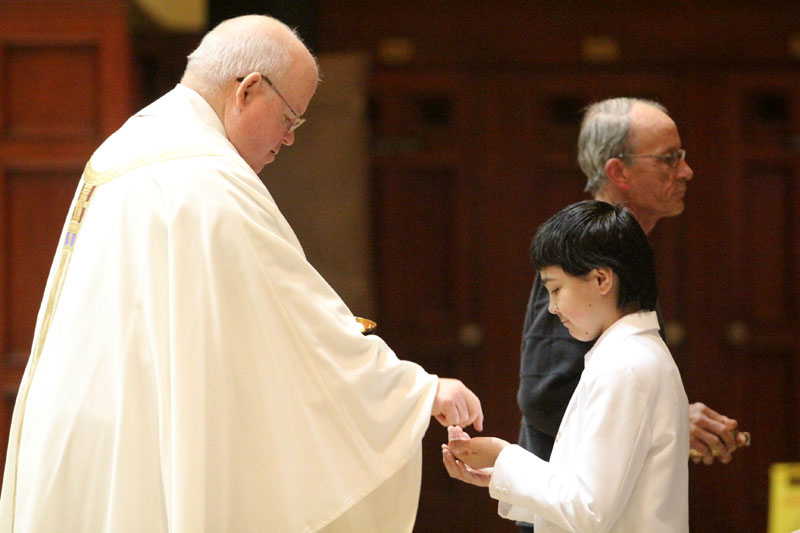 Fr John LaRosa gives communion to Robert Gallant for the first time