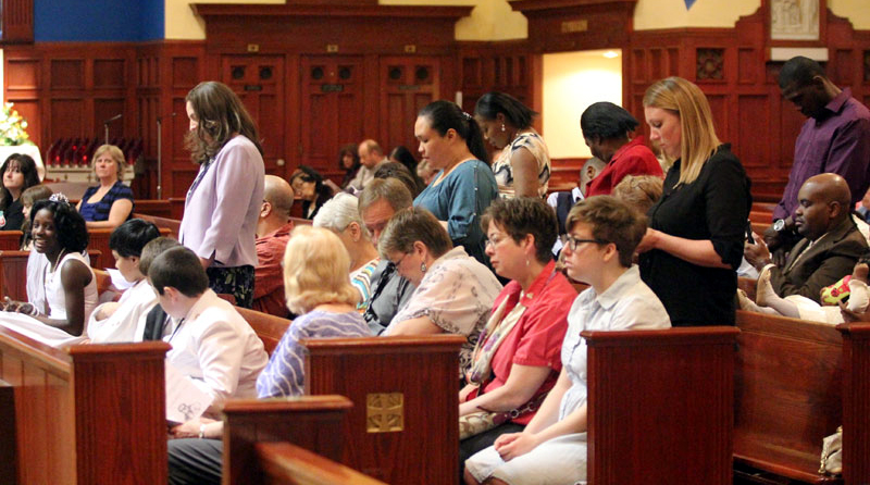 First communicant parents stand and pray for their children