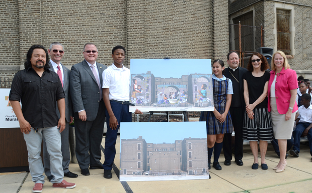 Artist Cesar Viveros (left) who designed the mural for St. Malachy School, stands with school students and administration, plus World Meeting of Families' officials. (Sabina Pierce)