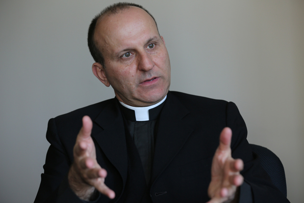 Father Paul Check, executive director of Courage, conducts an interview with CNS in Washington May 22. (CNS photo /Bob Roller)