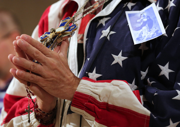 A worshiper holding a rosary and crucifix prays during a July 4, 2014 Mass celebrated at the Basilica of the National Shrine of the Immaculate Conception in Washington on the final day of last year's Fortnight for Freedom campaign. (CNS photo/Bob Roller)
