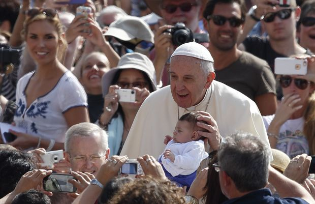 Pope Francis greets a baby as he arrives to lead his general audience in St. Peter's Square at the Vatican May 20. (CNS photo/Paul Haring)