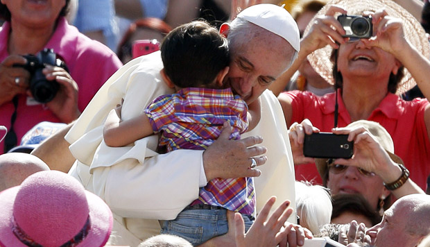 Pope Francis hugs a child as he arrives at the general audience in St. Peter's Square at the Vatican May 13. (CNS photo/Paul Haring)