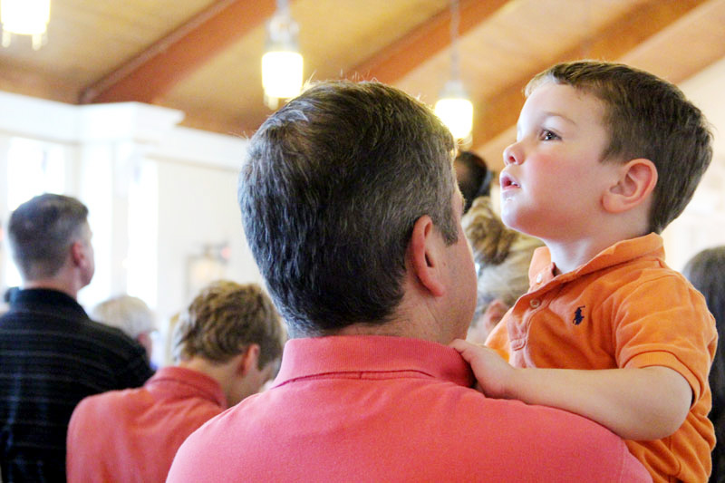 a young boy looks up at the choir as it fills the church with music
