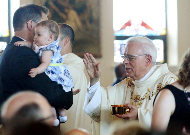 Msgr John Marine offeres a blessing to a little one after giving communion to her father