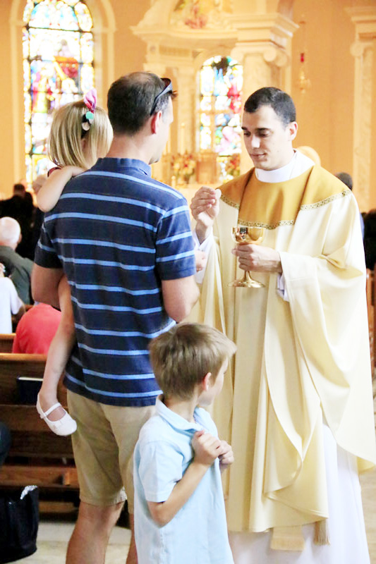 Newly ordained Fr Daniel Arechebala, who served his diaconate year at St Bede, distributes holy communion
