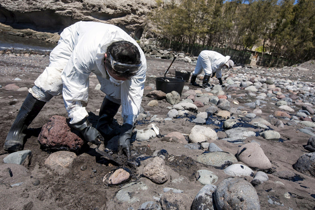 Men collect fuel oil from rocks April 23 following an oil spill along Veneguera beach in Spain's Canary Islands. Few papal encyclicals have been as eagerly awaited as Pope Francis' statement on the environment. (CNS photo/Borja Suarez, Reuters)