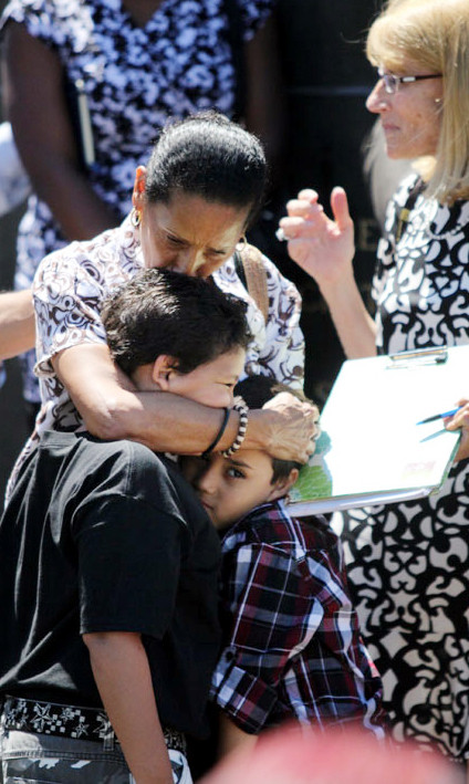 Maria Guzman kisses her grandsons Jesus and Christopher Terreforte at the launch of the Francis Fund. Guzman, a widow who while raising her grandchild was helped by Visitation Community Center in Kensington, now serves on the Hunger and Homelessness Committee. (Sarah Webb)
