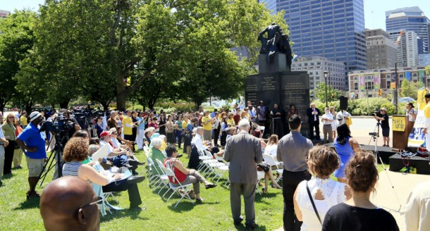 Maria Guzman speaks to the gathering on the parkway where Pope Francis will visit during his trip to Philadelphia in September. (Sarah Webb)