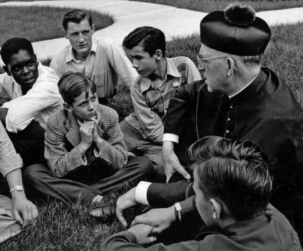 Father Edward Flanagan, the Irish-born priest who founded Boys Town in Nebraska, talks with a group of boys in this undated photo. (CNS photo/courtesy Boys Town)