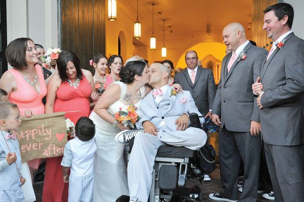 Newlyweds Amanda and Andres Gonzalez exchange a kiss on the front steps of Our Lady of Guadalupe Church in New Orleans May 22, nine years to the day that then-Officer Gonzalez was shot in the line of duty. (CNS photo/Peter Finney Jr., Catholic Herald)