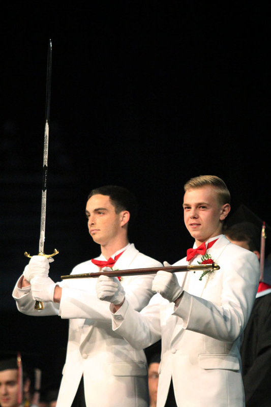 the incoming officers receive the swords from the outgoing graduation officers