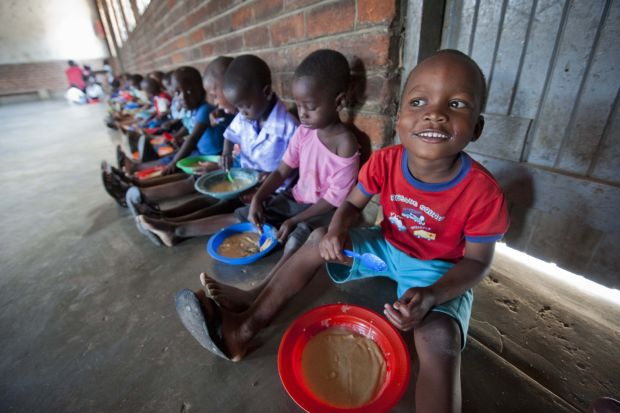 Children are seen in 2012 eating food provided by Mary's  Meals at a center in Malawi. Mary's Meals, a global child hunger charity founded by Scotsman Magnus MacFarlane-Barrow, provides meals to children around the world every school day. The program recently served its 1 millionth meal. (CNS photo/courtesy Chris Watt)