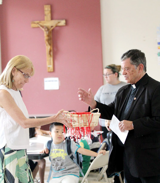 Anne Ayella, from NDS, holds a basket of peace necklaces as Msgr. Daniel Sullivan, President of the NDS Board, blesses them.