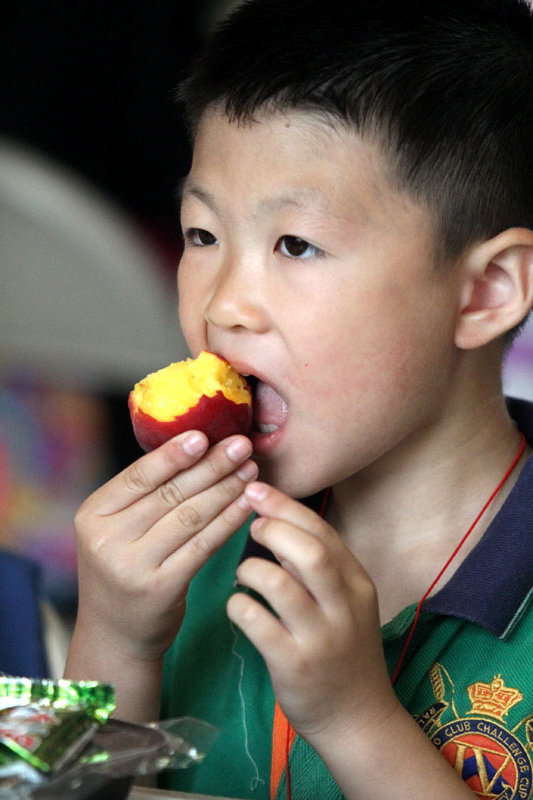 Sam Liu takes a bite out of his juicy peach.