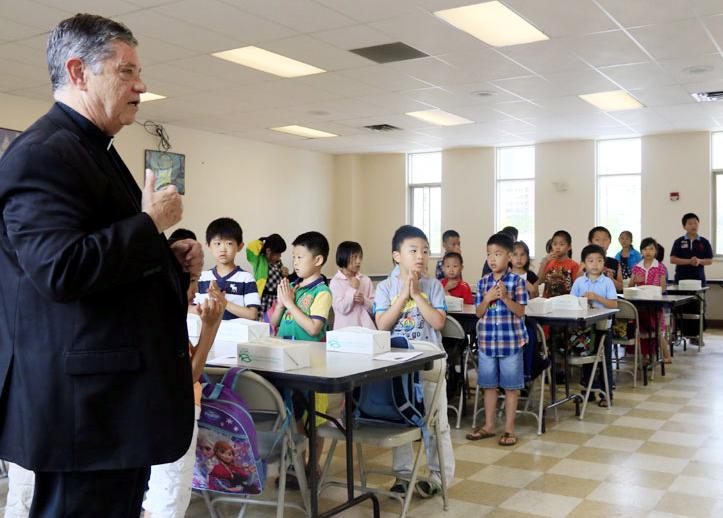 Msgr. Daniel Sullivan leads the children in pray before lunch.