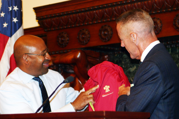 Mayor Michael Nutter, left, trades his suit jacket for a bright red World Meeting of Families jacket, courtesy of Aramark Corp.'s Ceo Eric Foss, June 1 at Philadelphia City Hall.
