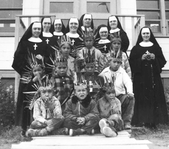 In this 1960 photo, Sacred Heart of Ottawa Sisters pose with students at the Pukatawagan Residential School in Manitoba. (CNS photo/Library and Archives Canada, Reuters)