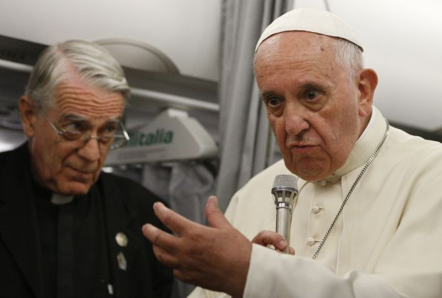 Pope Francis speaks to journalists aboard his flight from Sarajevo, Bosnia-Herzegovina, to Rome June 6. At left is Jesuit Father Federico Lombardi, the Vatican spokesman. The pope announced on the return flight that a decision soon will be announced concerning alleged Marian apparitions in Medjugorje, Bosnia-Herzegovina. (CNS photo/Paul Haring)