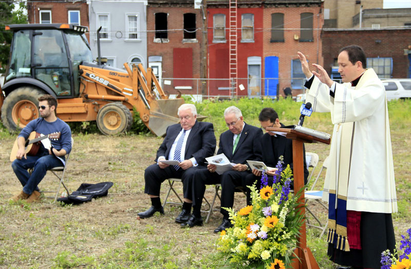 Bishop John McIntyre blesses the ground where St Francis Inn Senior Housing will be bulit.